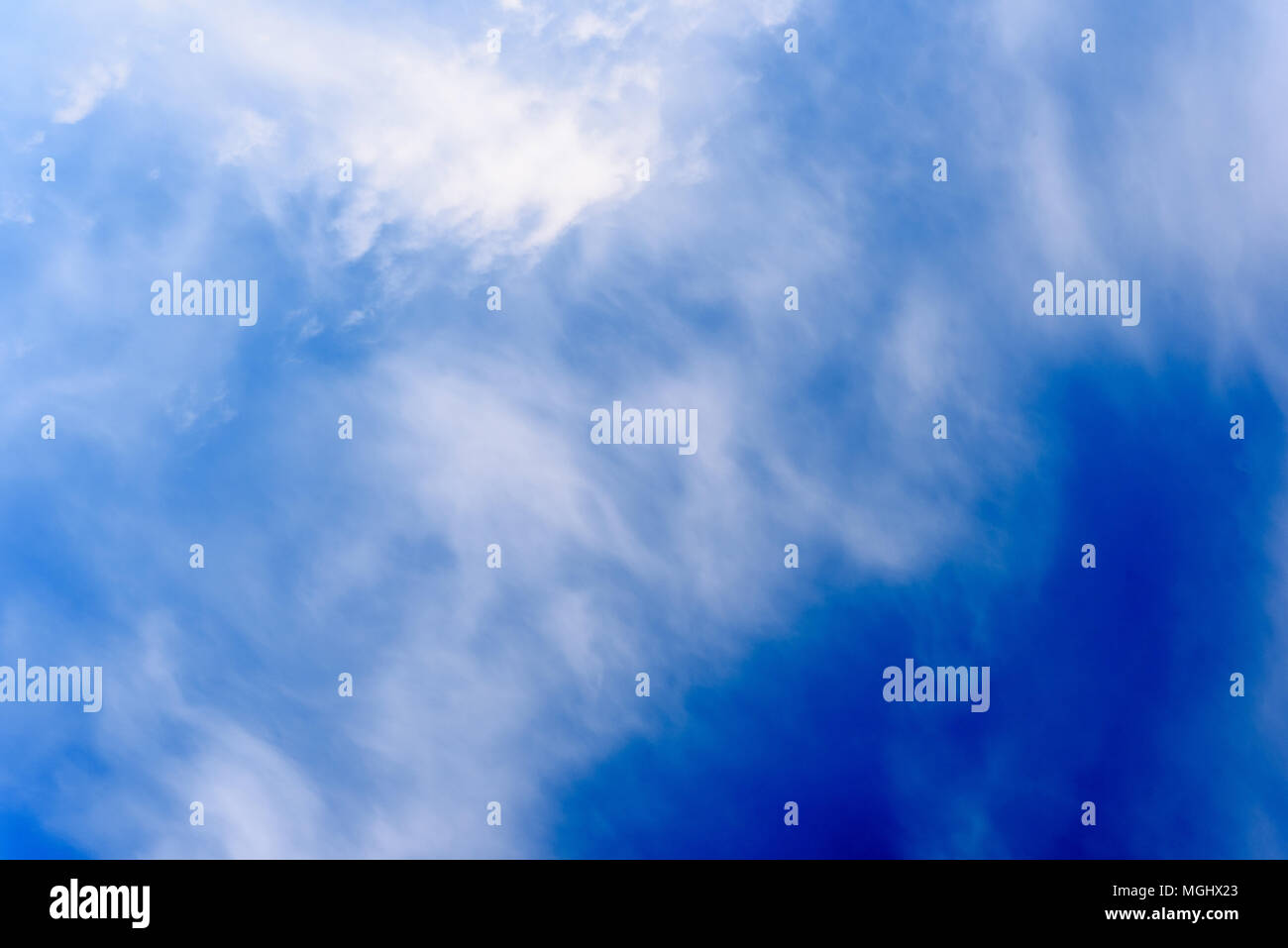 Wispy white clouds and turbulent sky taken during a winter's day with crisp blue areas of natural skyline Stock Photo