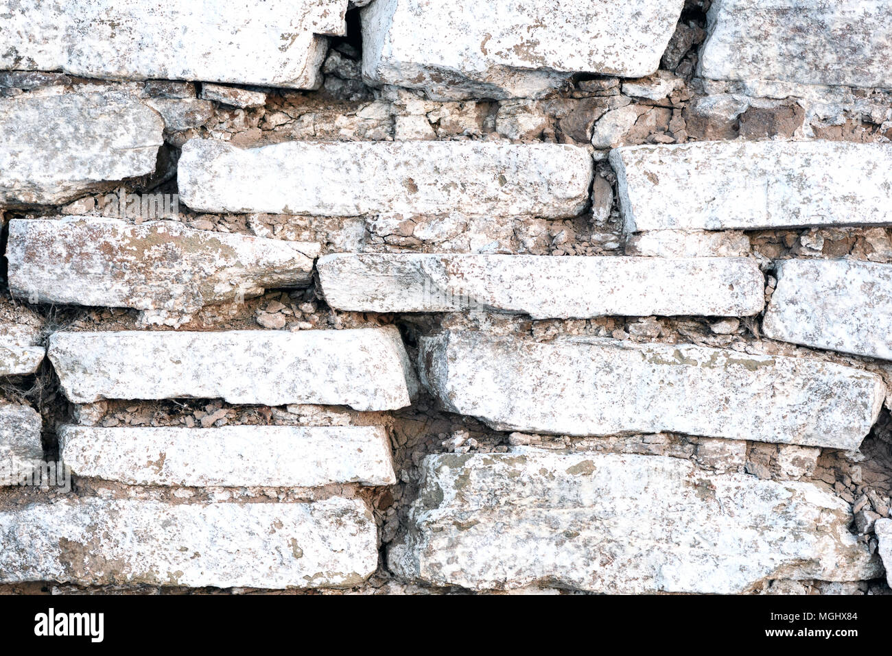 Old stacked tile wall with white wash paint in an old worn state Stock Photo