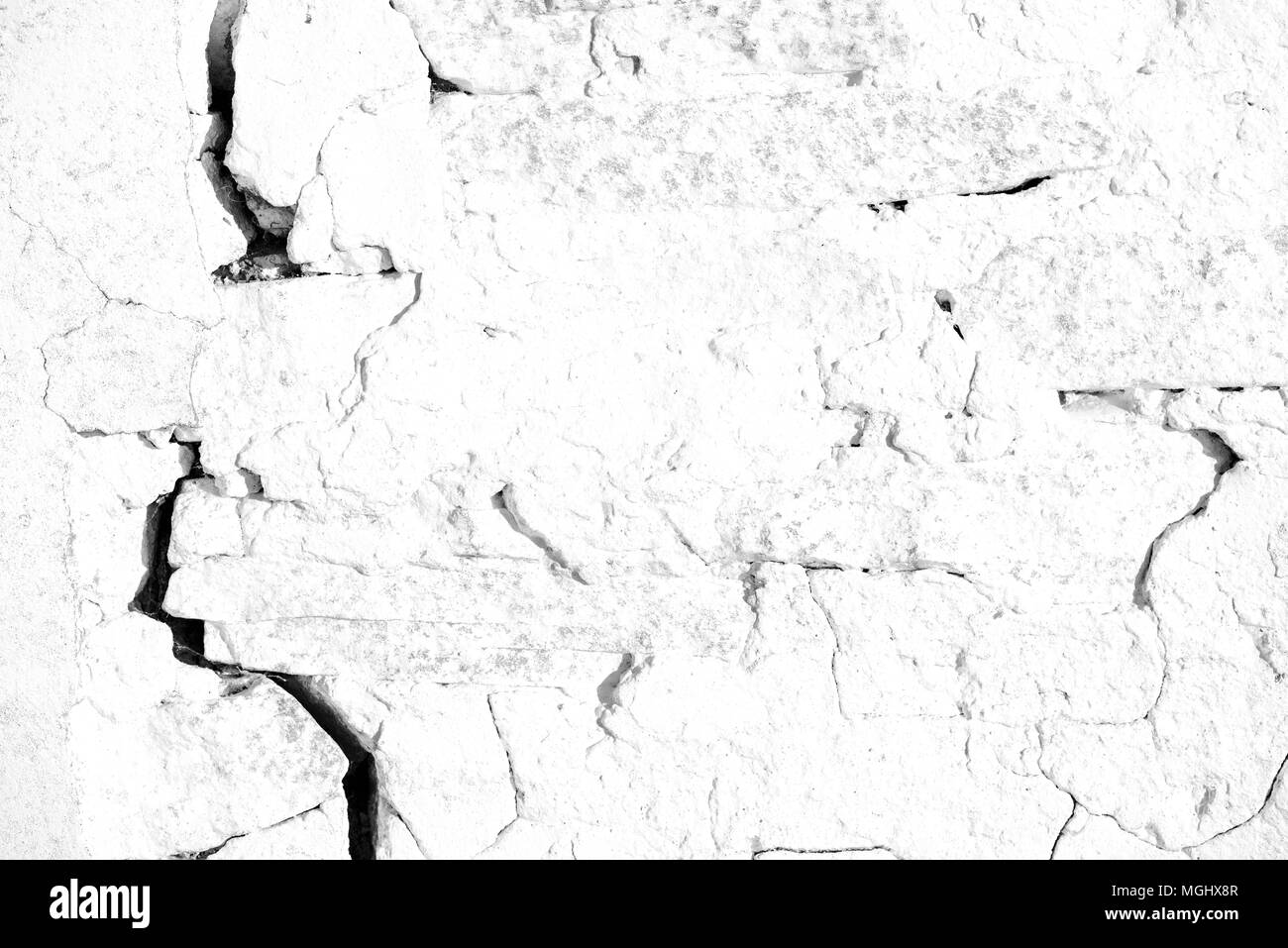 Old cracked plaster wall with lines of broken plastering due to age and decay of the vintage construction work Stock Photo
