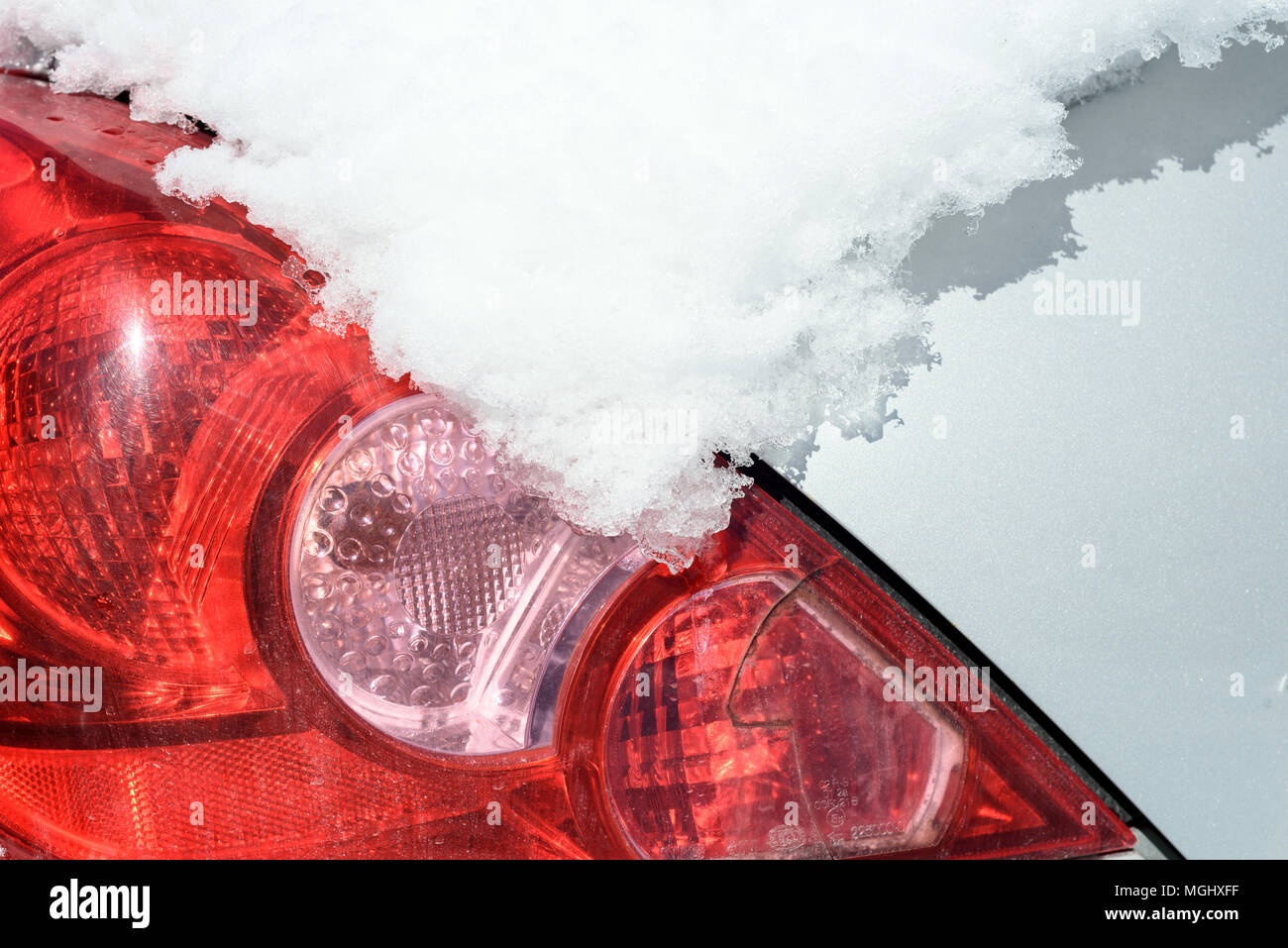 Car rear view light and indicator covered and obscured in a thick blanket of winter snow. Copy space area for extreme weather travel and transport con Stock Photo