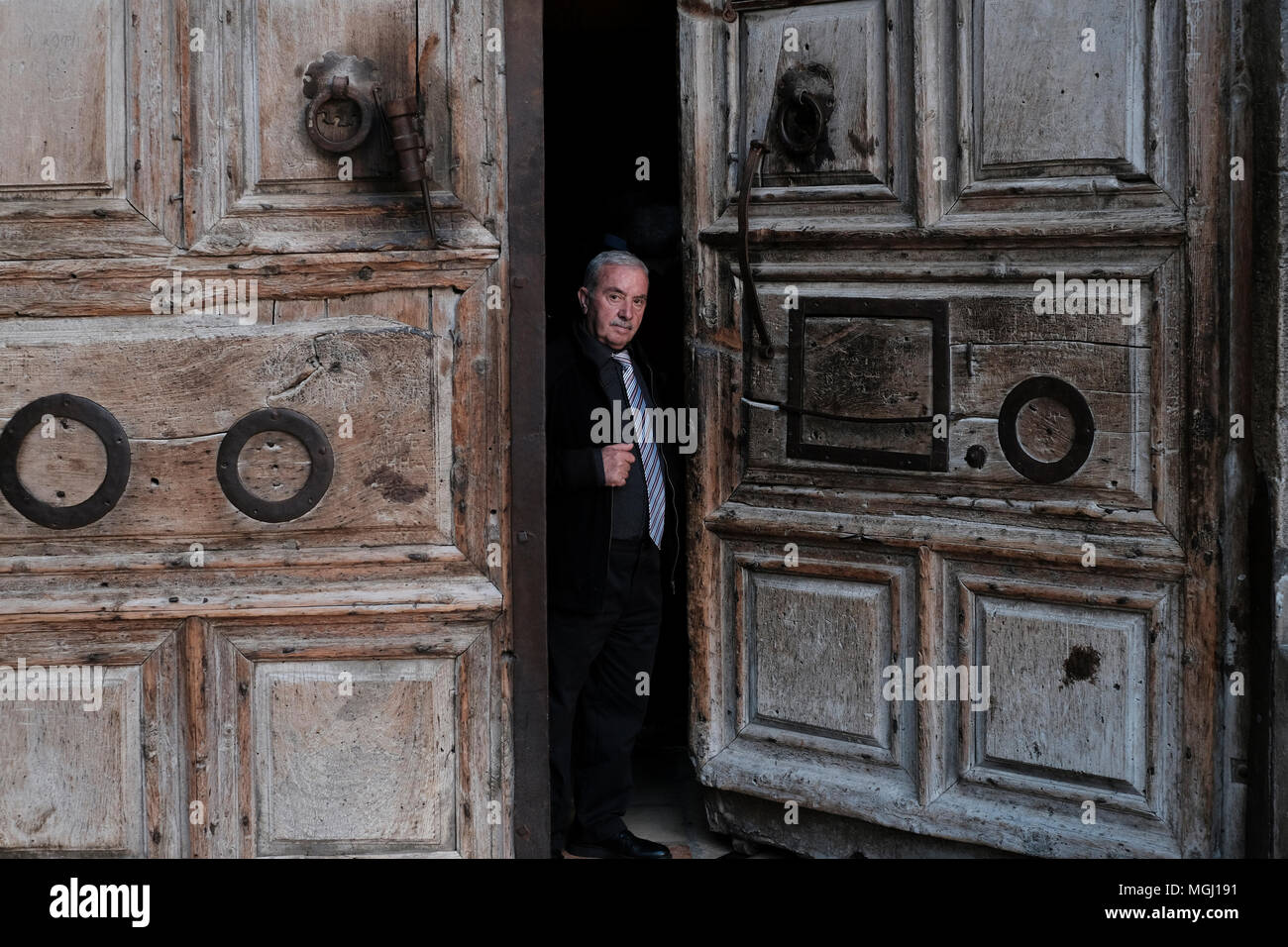 Wajeeh Nuseibeh, a Muslim whose family has opened and closed the Holy Sepulcher since the Ottoman era closing the doors of the church of Holy sepulchre in old city East Jerusalem Israel. The custody of the door and the key for the Church of the Holy Sepulchre is entrusted to two Muslim families (Nuseibeh and Judeh) and it has been like this for centuries. - Stock Image