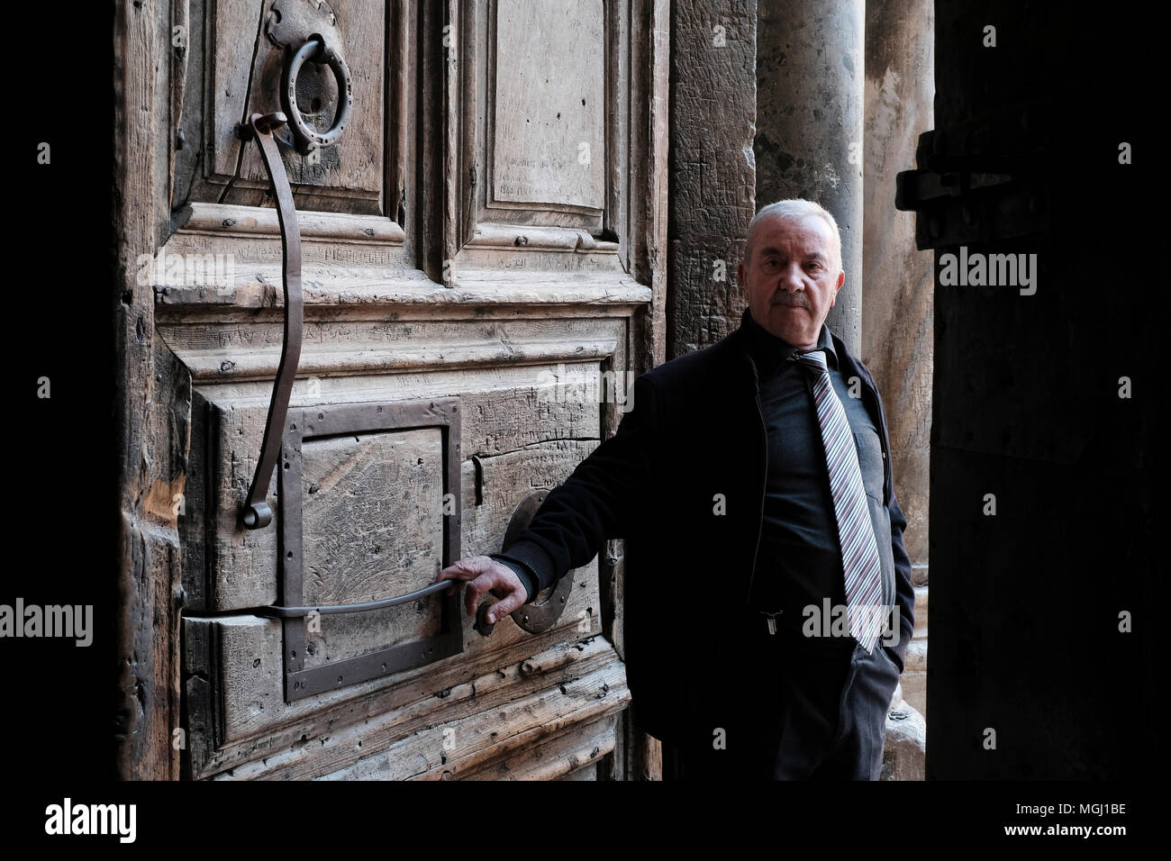 Wajeeh Nuseibeh, a Muslim whose family has opened and closed the Holy Sepulcher since the Ottoman era posing at the doors of the church of Holy sepulchre in old city East Jerusalem Israel. The custody of the door and the key for the Church of the Holy Sepulchre is entrusted to two Muslim families (Nuseibeh and Judeh) and it has been like this for centuries. - Stock Image
