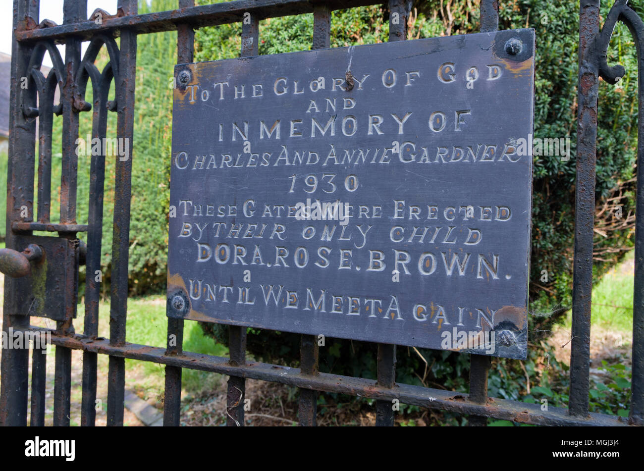 Sign on church gates indicating they were erected by Dora Brown in memory of her parents; Lower Shuckburgh, Warwickshire, UK - Stock Image