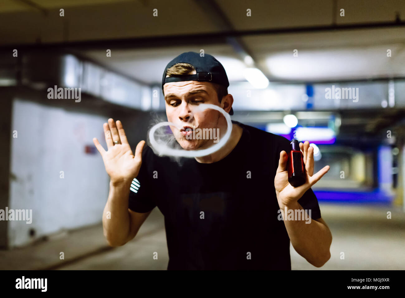 Man in cap smoke an electronic cigarette and releases clouds of vapor performing various kind of vaping tricks Stock Photo