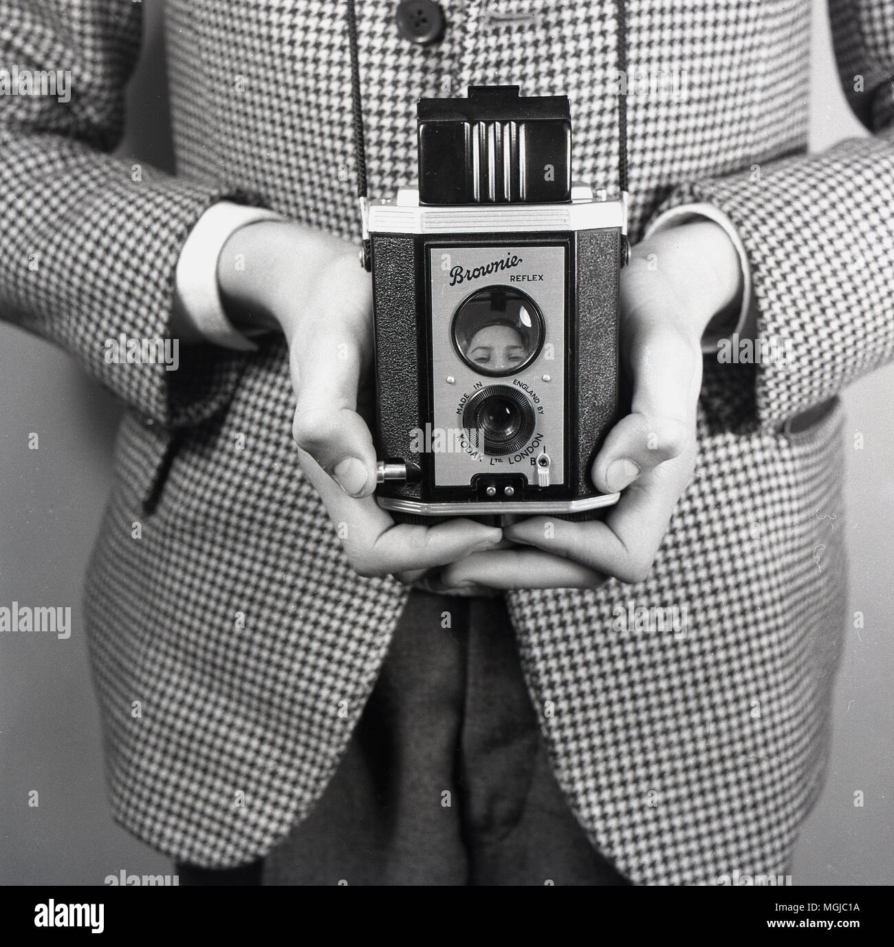 1950s, historical, young boy in sports jacket holding a Kodak Brownie Reflex film camera, England, UK. From 1946, this twin lens camera, with a folding hood, was made in England by Kodak Ltd of London until 1960. - Stock Image