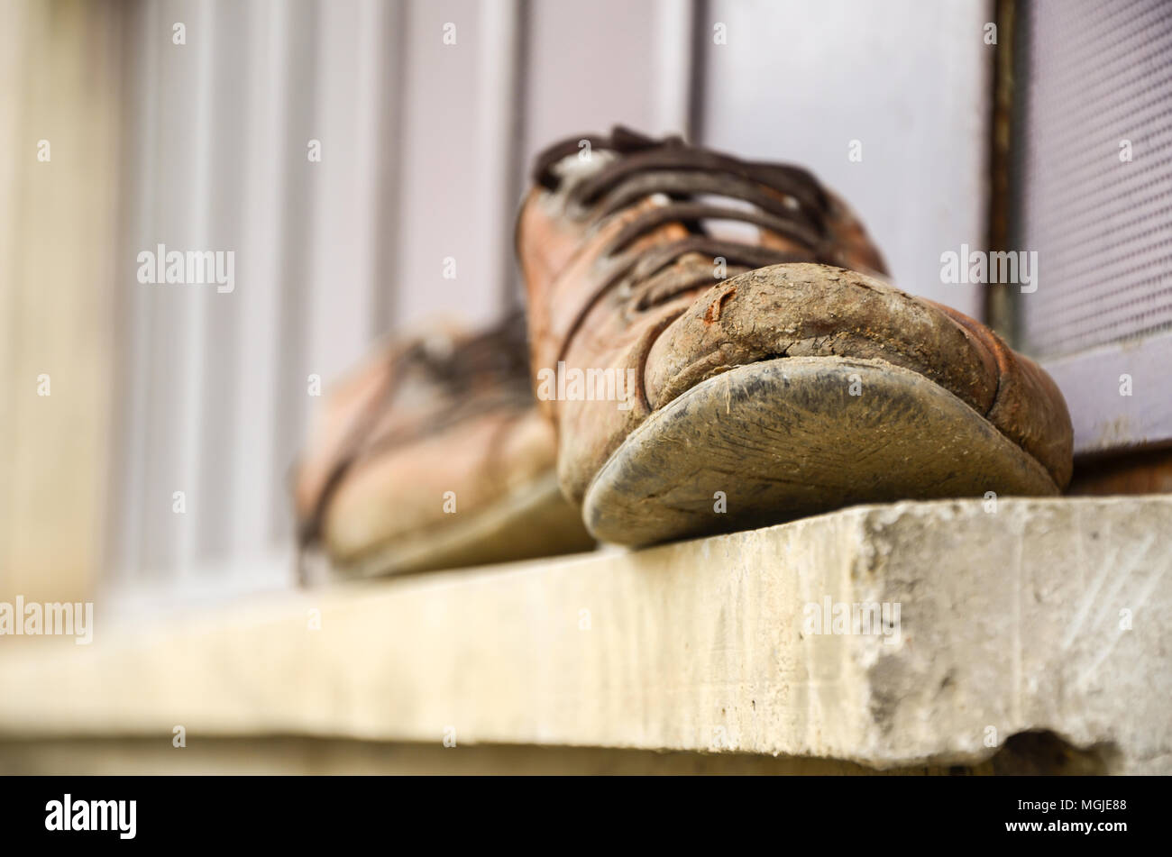 Muddy and old shoes in front of the window, worker's shoes, labor, soreness,selective focus - Stock Image