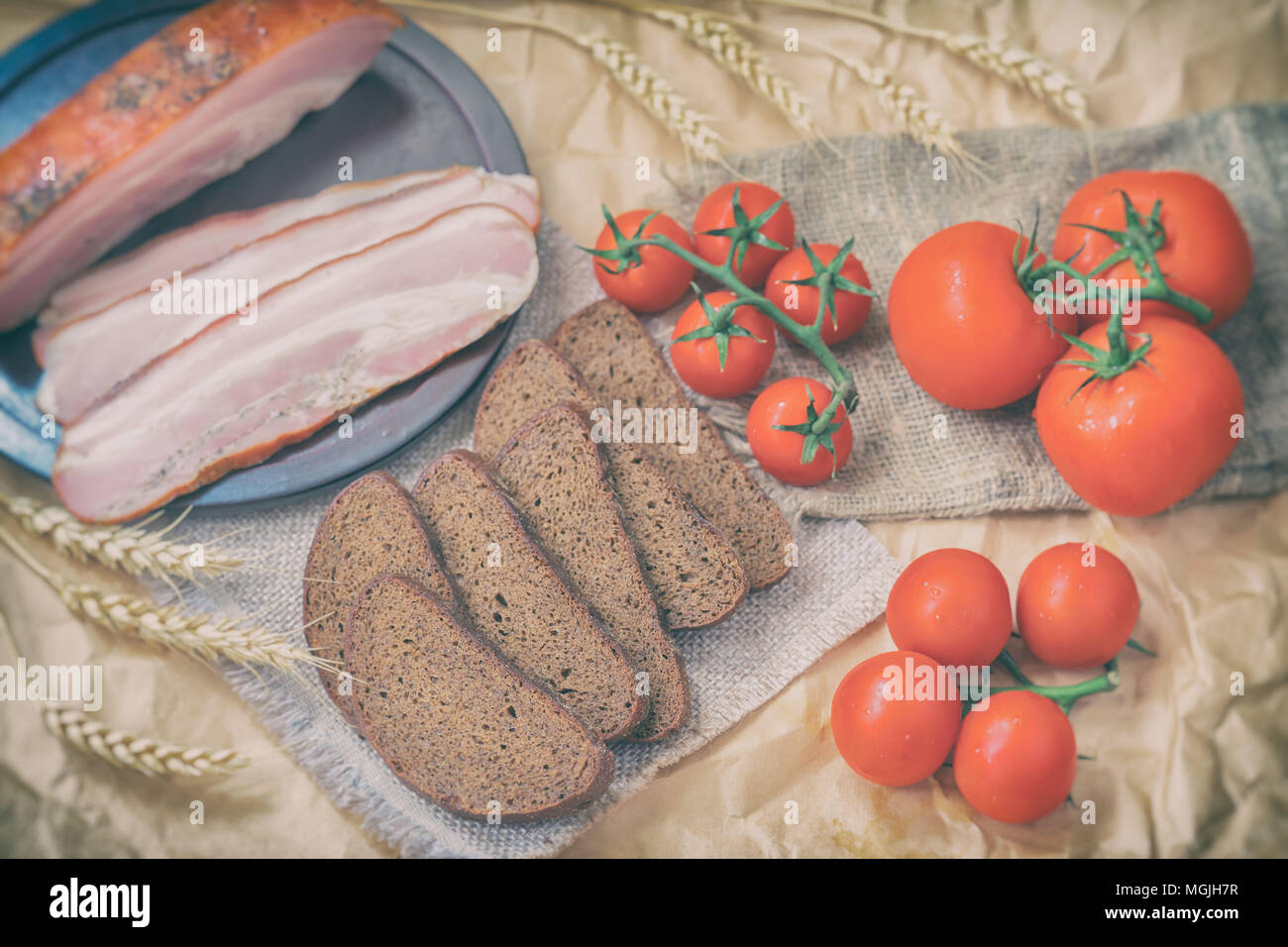 Close-up of slices of bacon, rye black bread, ripe red tomatoes on packaging craft paper. Top view. Fresh organic food. Quick tasty snack. Rustic styl - Stock Image