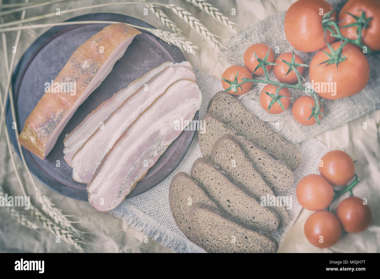Rustic style of fresh organic food. Quick tasty snack. Slices of bacon, rye black bread, ripe red tomatoes on napkin from burlar. Top view. Vintage ba - Stock Image