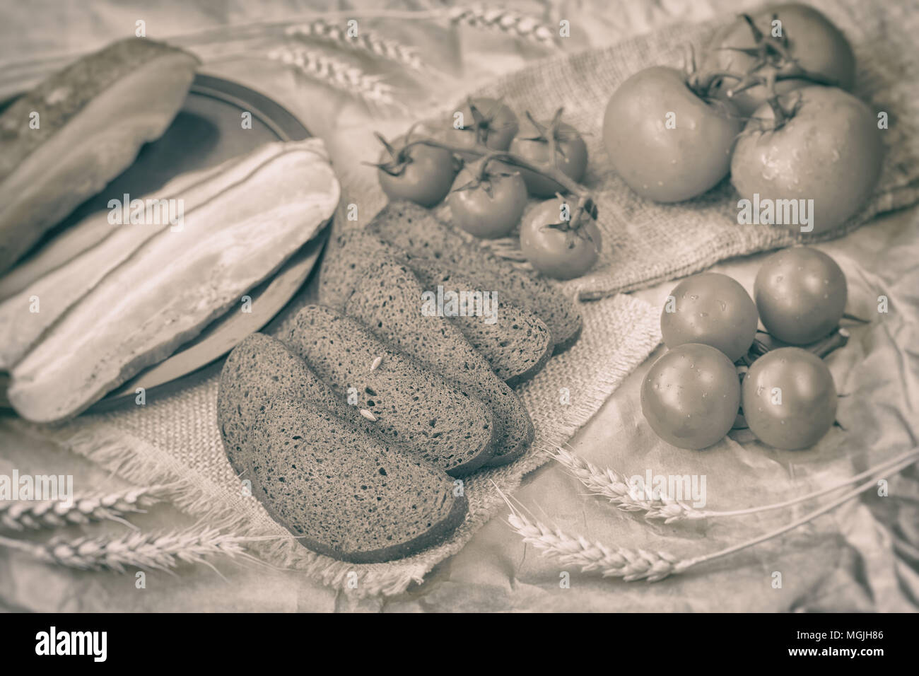 Vintage sepia style of fresh organic food. Traditional quick tasty snack. Slices of bacon, rye black bread, ripe red tomatoes on coarse burlap. Top vi - Stock Image