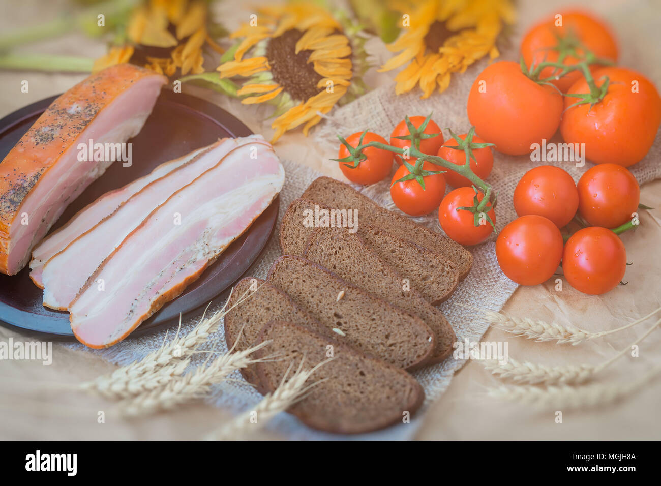 Vintage top view. Delicious slices of bacon, rye black bread, ripe red tomatoes on sackcloth, old sunflowers Top view. Fresh organic Food. Quick tasty - Stock Image