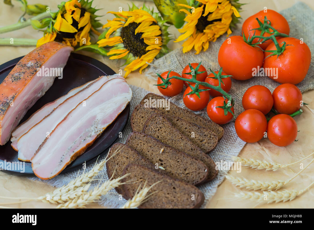 Delicious slices of bacon, rye black bread, ripe red tomatoes on sackcloth, old sunflowers Top view. Fresh organic Food. Quick tasty snack. For appeti - Stock Image