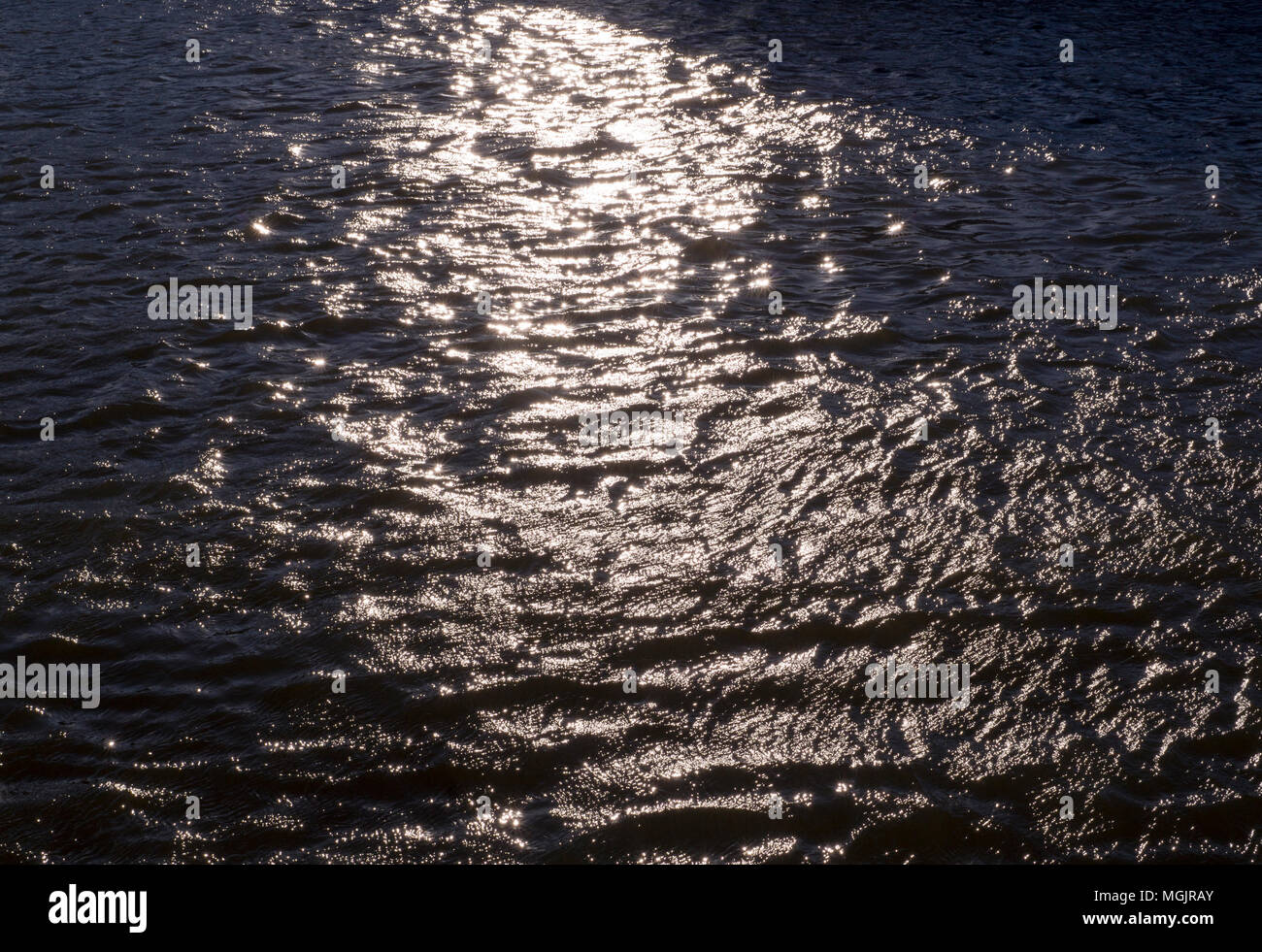 reflections of evening sun on rippled water in the river. background, texture, nature - Stock Image