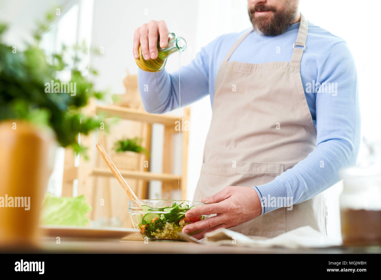 Bearded man wearing apron pouring olive oil into bowl with vegetable salad while preparing dinner for his family, interior of spacious kitchen on back - Stock Image
