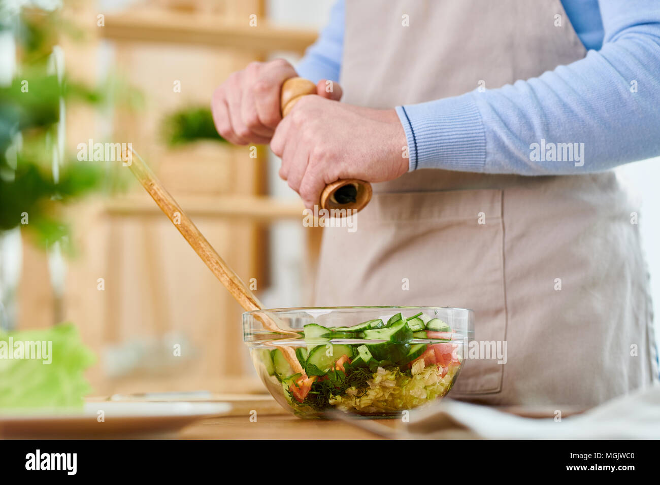 Unrecognizable man wearing apron seasoning vegetable salad with pepper while preparing festive dinner for his family, close-up shot - Stock Image