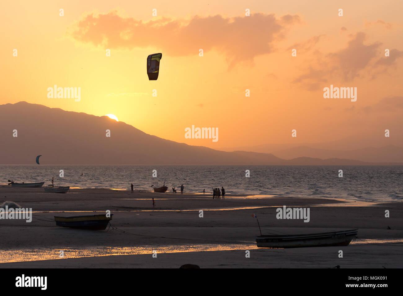 Kitesurfing around fishing boats during sunset at Punta Chame, Panama - Stock Image