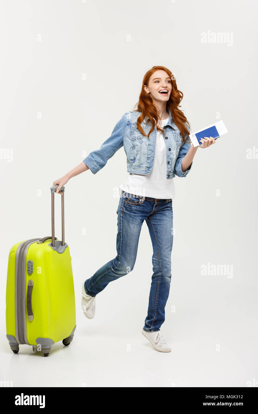Travel Concept: Young Caucasian Woman traveler with suitcase isolated on white background. - Stock Image