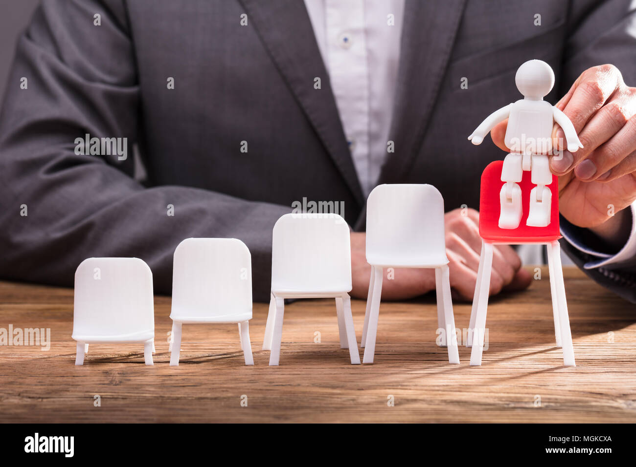 Close-up Of A Businessperson's Hand Placing Human Figure On Red Chair Over Wooden Desk Stock Photo