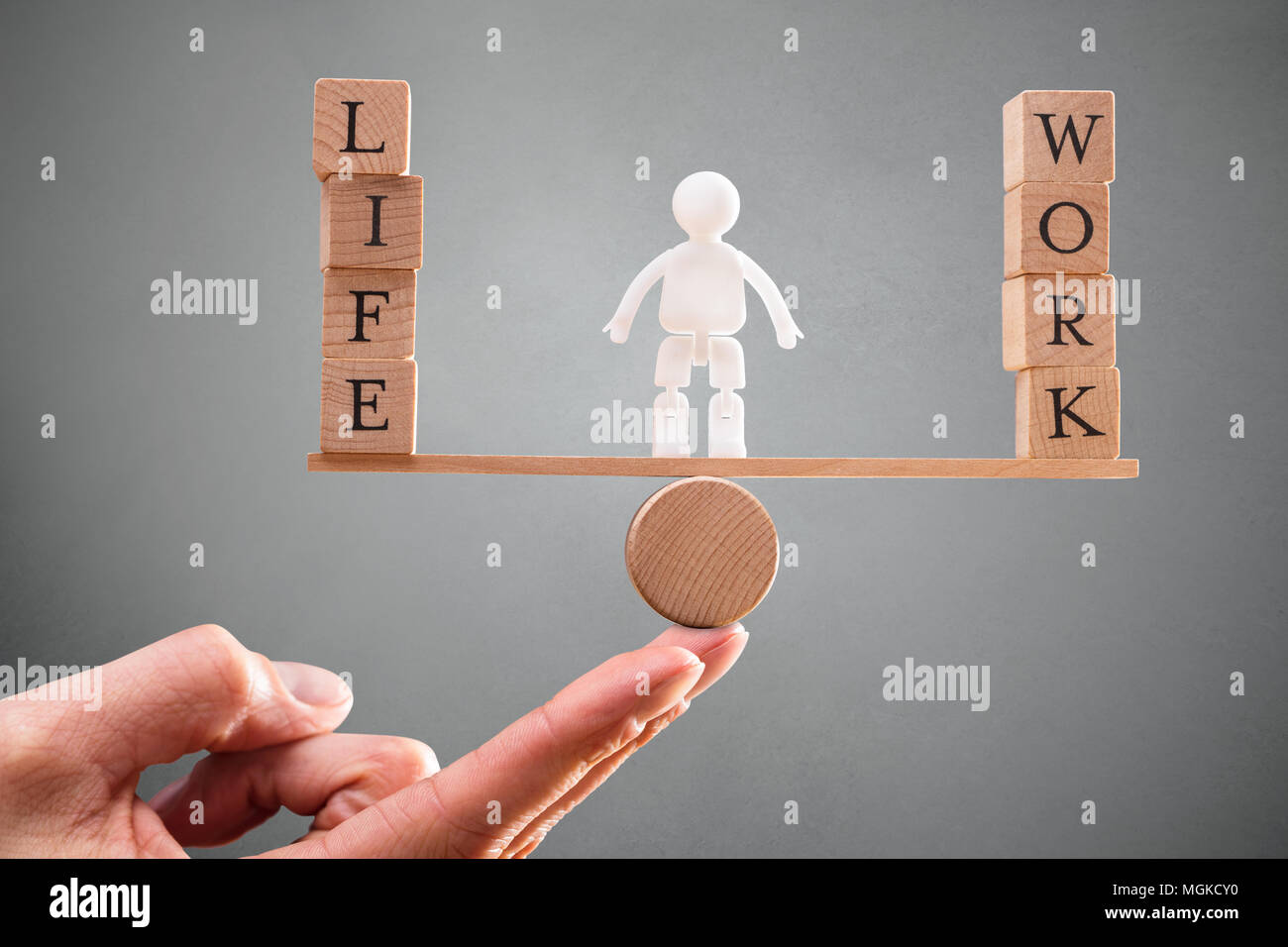 A Person's Hand With Human Figure Standing Between Work And Life Wooden Blocks On Seesaw - Stock Image
