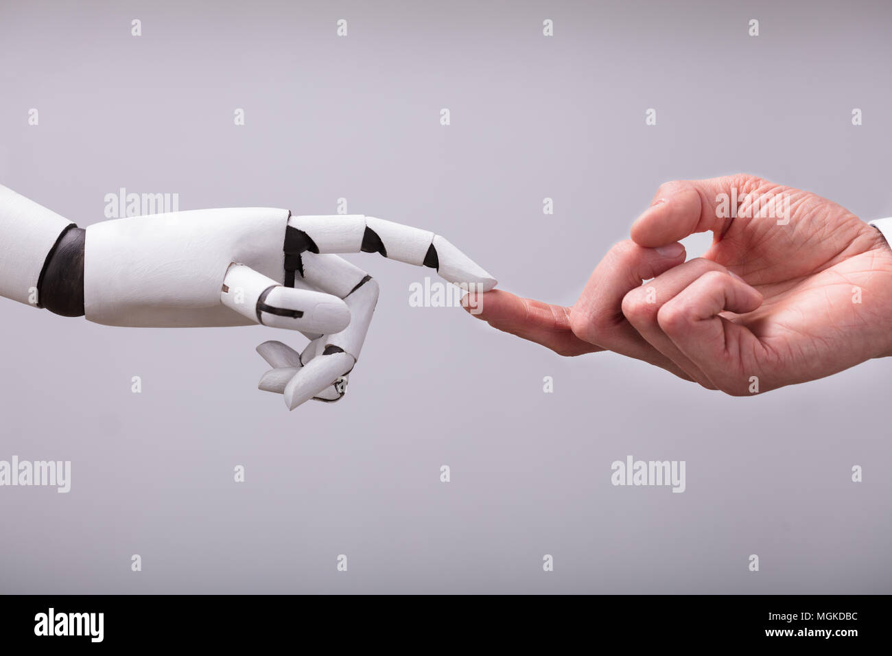 Robot Touching Human Finger Against Gray Background - Stock Image