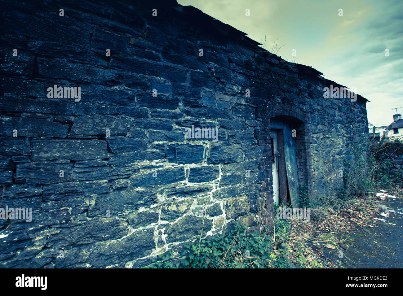 Derelict barn on british countryside.Dark and moody image of empty building,great book cover,instagram style filters.Abandoned building in North Wales. - Stock Image