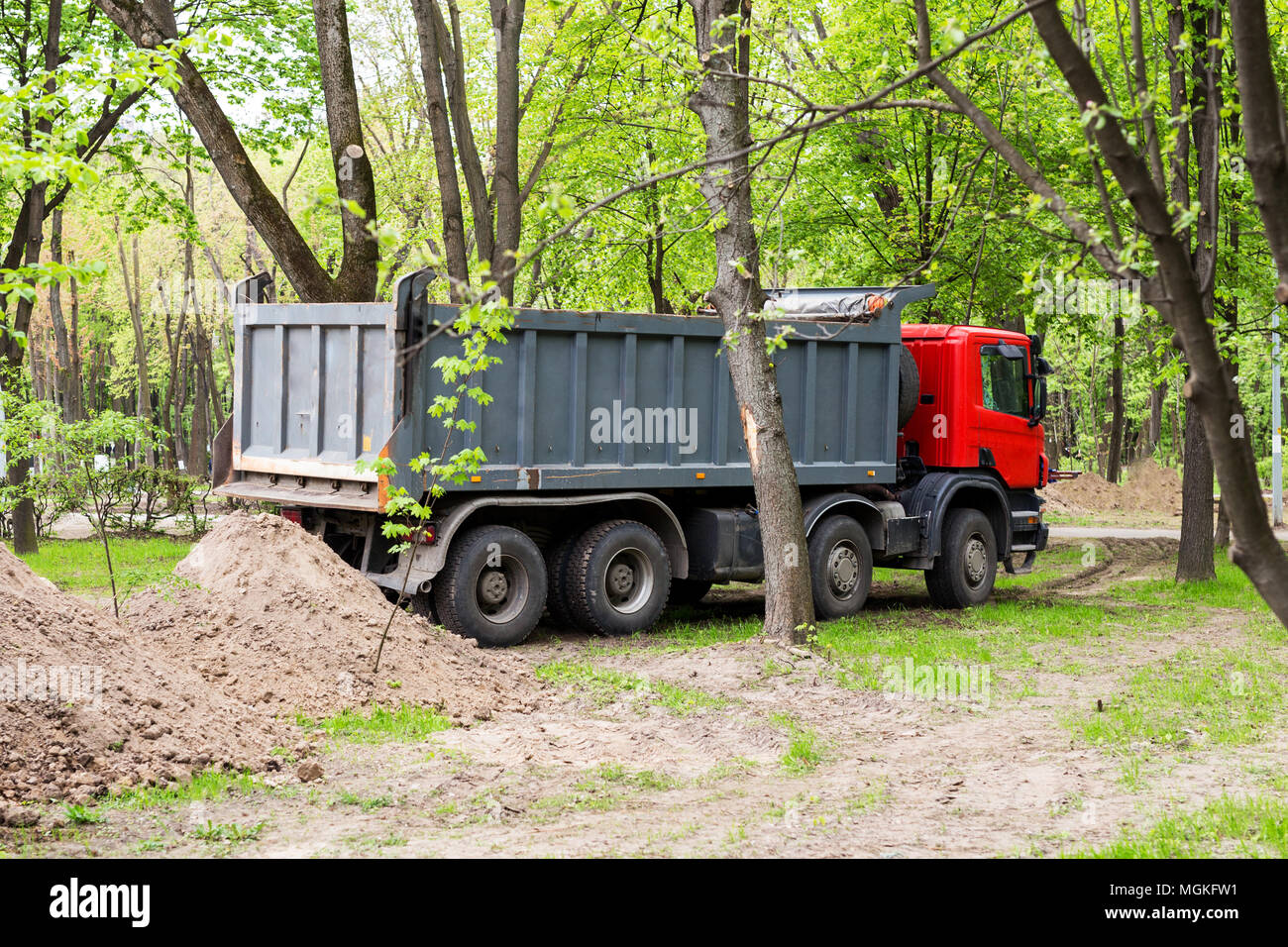 Big tipper truck near soil heap. Reconstruction of city park with heavy machinery - Stock Image