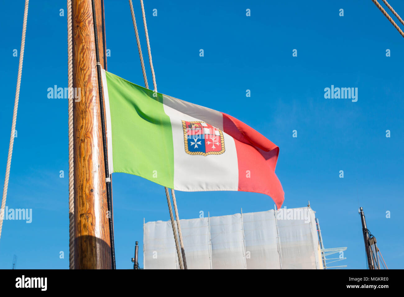 The italian army flag on a wooden boat flagpole on a sunny day in cesenatico. - Stock Image