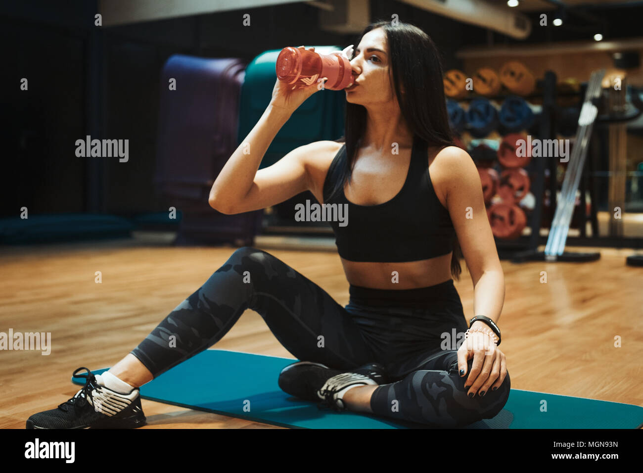 Young attractive brunette girl relaxing and drinking water at gym on the blue yoga mat after workout. Stock Photo