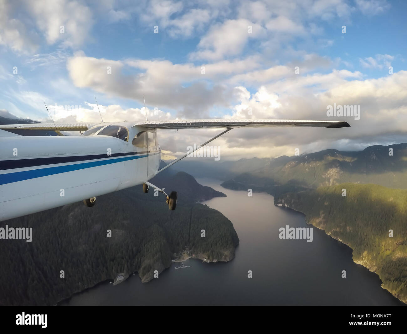 Small Airplane Flying Over Deep Cove During A Vibrant Sunset Taken In Vancouver British Columbia Canada