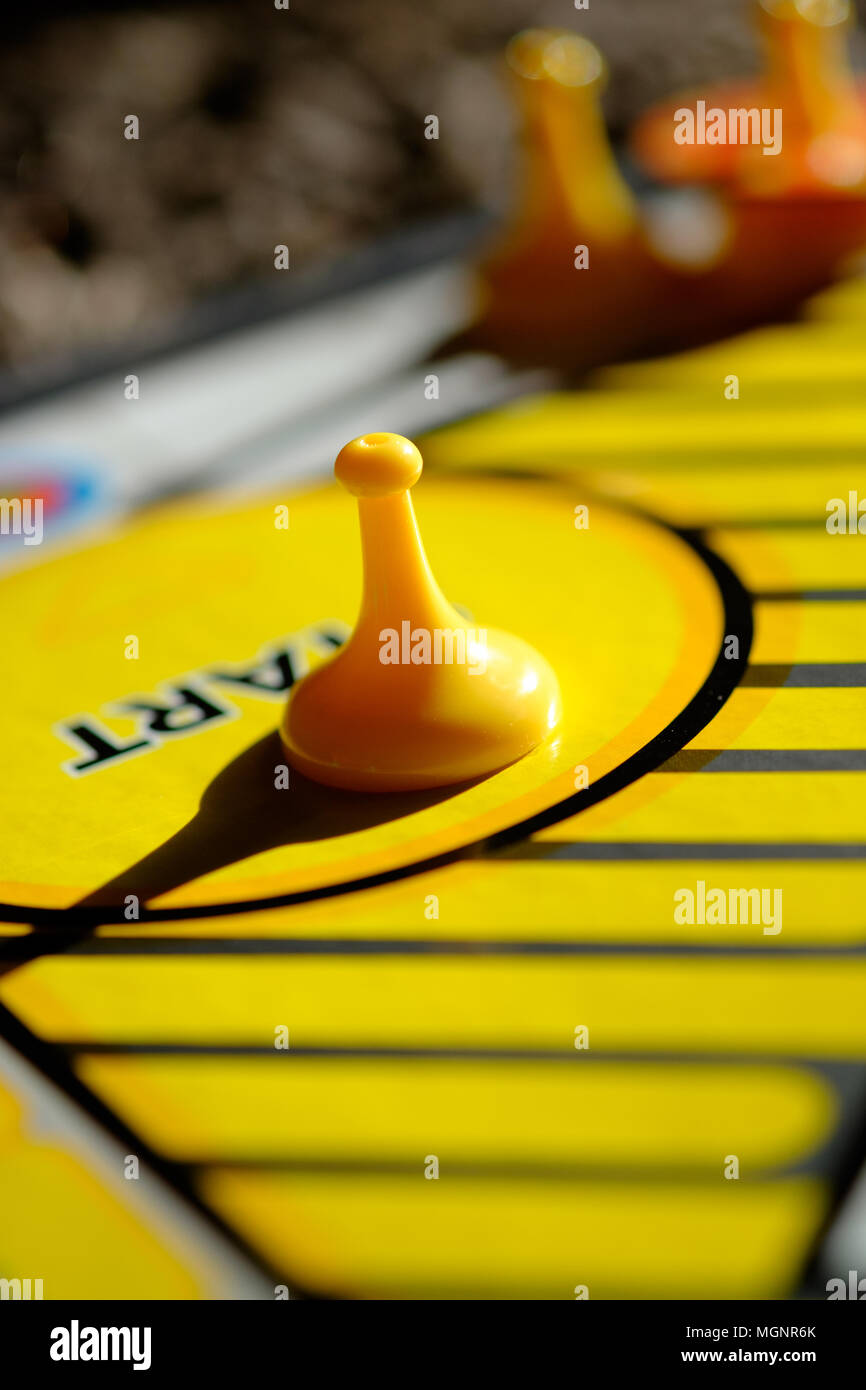 Board game with yellow marker at the starting position, symbolic of making a start, beginning, commencing an activity or journey - Stock Image