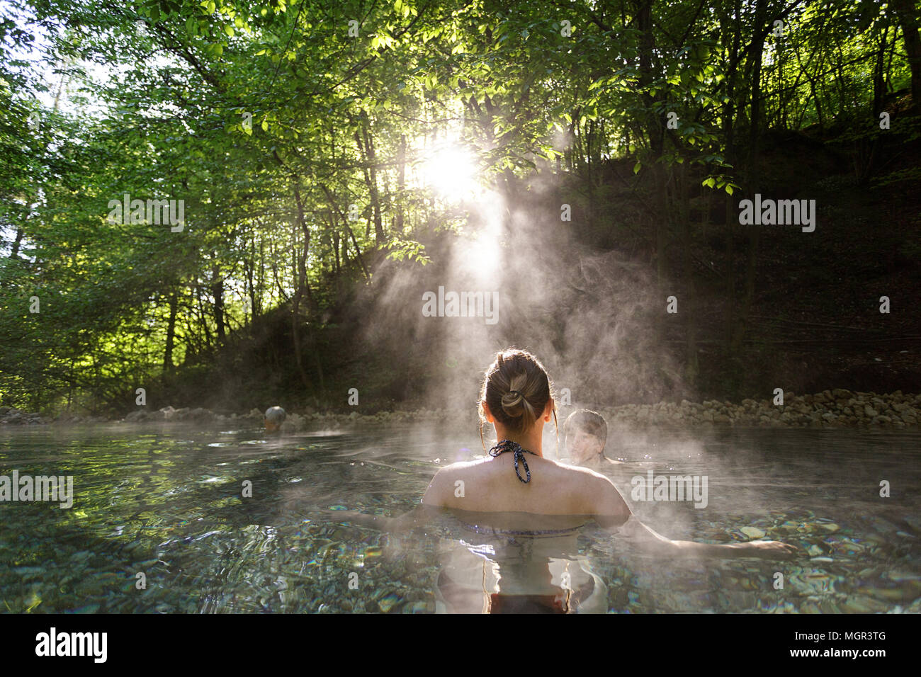 Woman relaxing in natural hot spring in the forest, Maibachl, Austria, Europe. Stock Photo