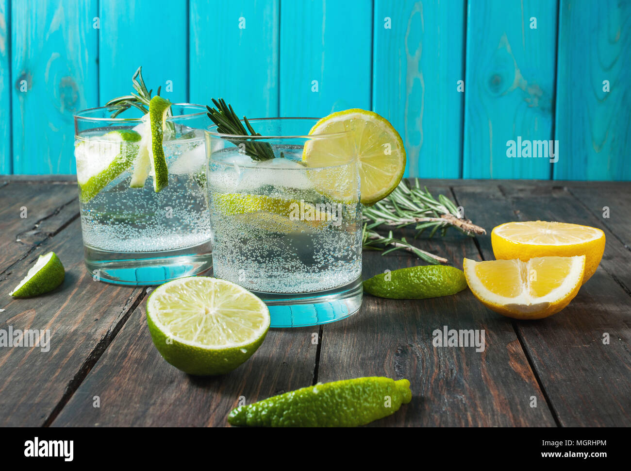 Alcoholic drink gin tonic cocktail with lemon, rosemary and ice on rustic wooden table, copy space Stock Photo