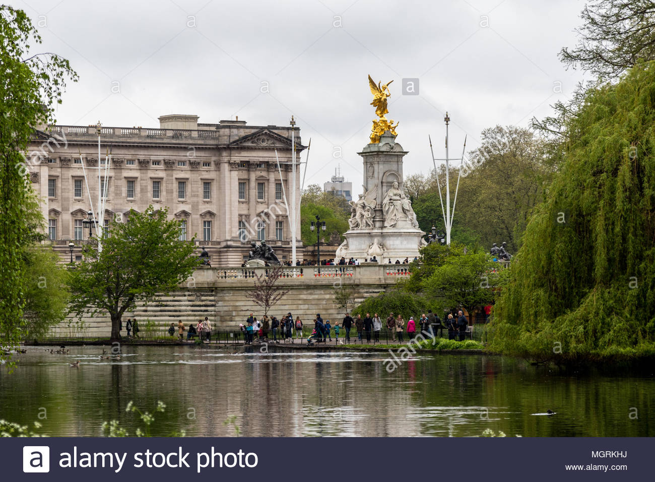 Tourists walk beside the lake in St James Park in the shadow of the Victoria Monument and Buckingham Palace on an overcast day in London. - Stock Image