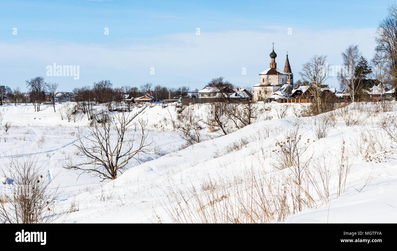 cityscape of Suzdal town with Holy Cross Exaltation and St Cosmas and St Damian Churches in Korovniki district on riverbank of frozen river in winter  - Stock Image
