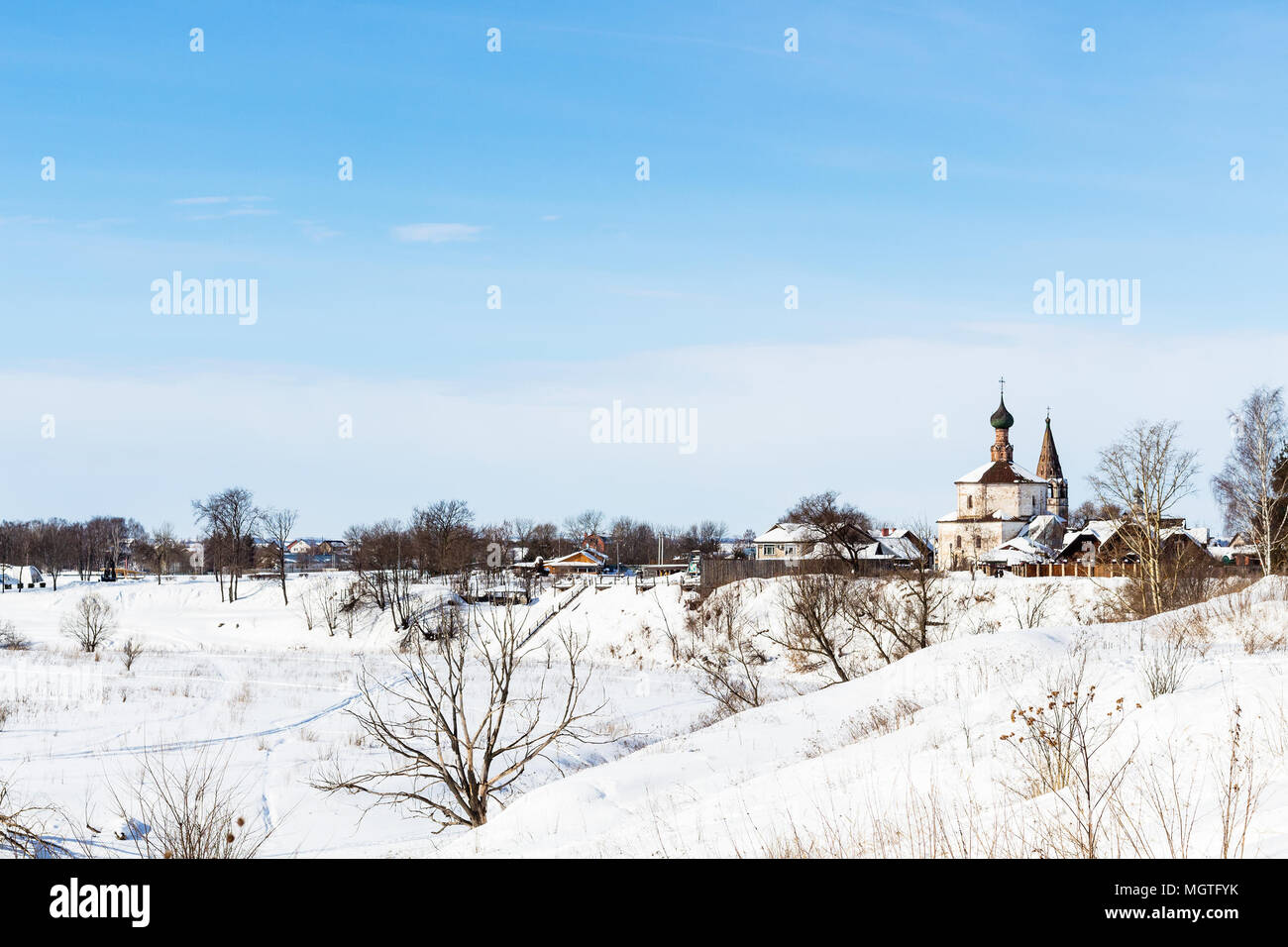 view of Suzdal town with Holy Cross Exaltation and St Cosmas and St Damian Churches in Korovniki district on riverbank of frozen river in winter in Vl - Stock Image
