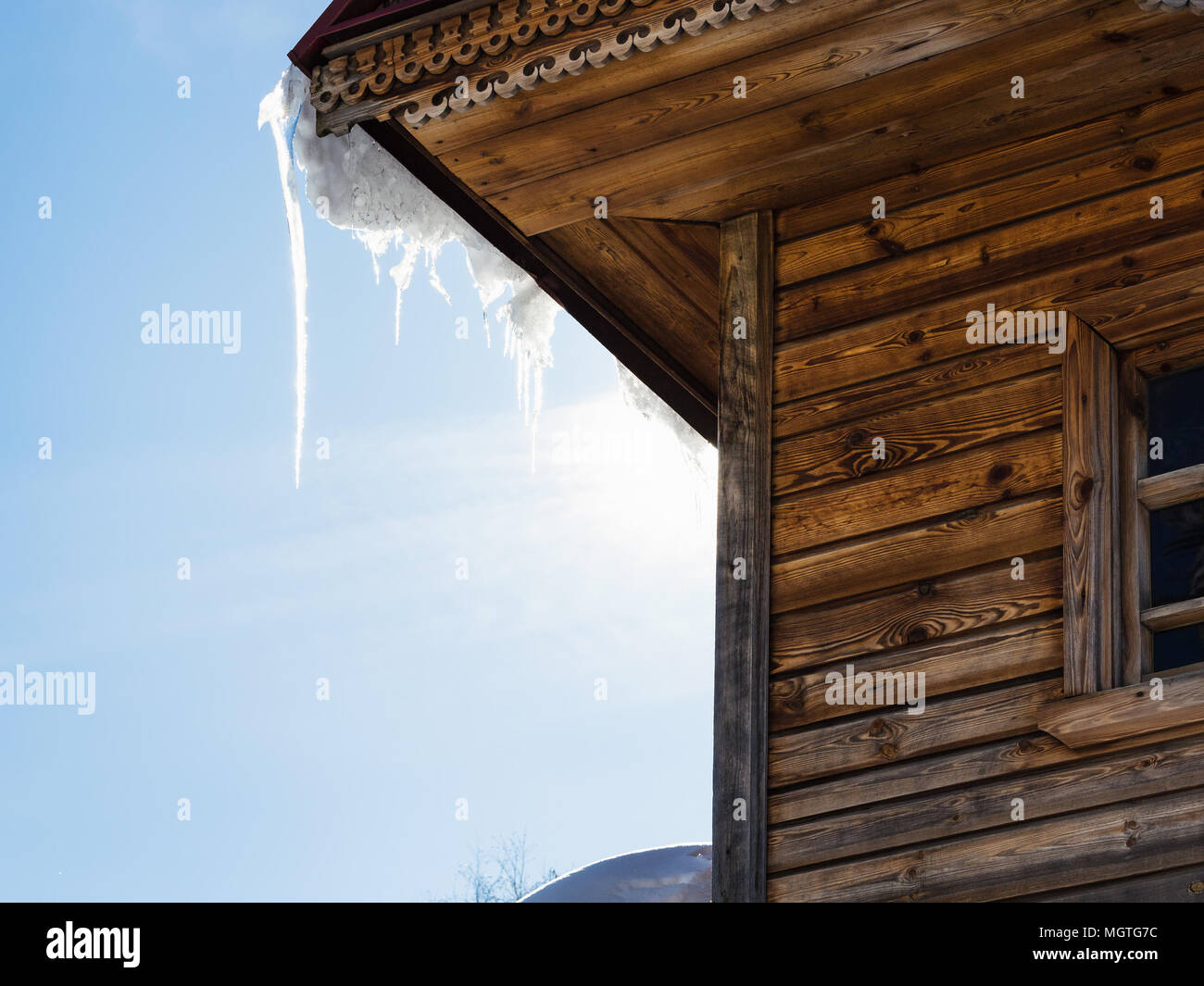 icicle illuminated by sun on roof of old log house in Suzdal town in