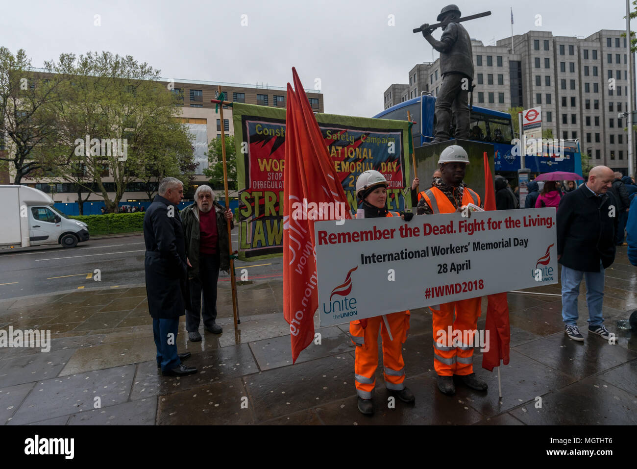 London, UK. 28 April 2018.  Unite workers pose with a large poster 'Remember the Dead. Fight for the Living' at the start of the International Workers' Memorial Day rally at the statue of a building worker on Tower Hill remembering all those killed at work, around 500 in the last ten years, mainly in the construction industry, as well as those injured, disabled and made unwell, almost all in preventable incidents. Credit: ZUMA Press, Inc./Alamy Live News - Stock Image