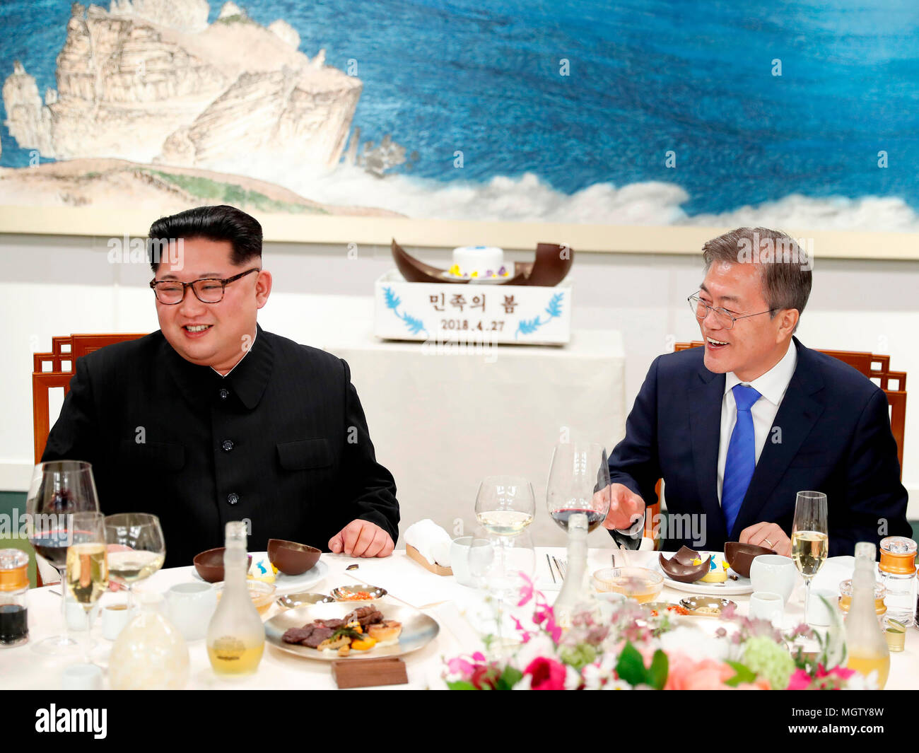 Moon Jae-In and Kim Jong-Un, Apr 27, 2018 : South Korean President Moon Jae-In (R) and North Korean leader Kim Jong-Un use mallets to open Mango mousse decorated with a flag symbolizing an unified Korean Peninsula, during a banquet after the historic inter-Korean summit at the Peace House of the Panmunjom in the Demilitarized Zone (DMZ) separating the two Koreas in Paju, north of Seoul, South Korea. The historic summit ended on April 27 with calls for the complete denuclearization of the Korean Peninsula and an immediate halt to all hostile acts, local media reported. EDITORIAL USE ONLY (Photo Stock Photo