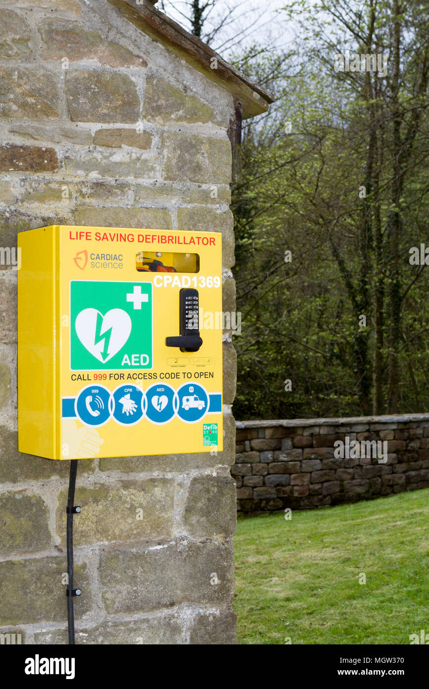 A wall mounted heart defibrillator for emergency resuscitation of a heart attack victim - Stock Image