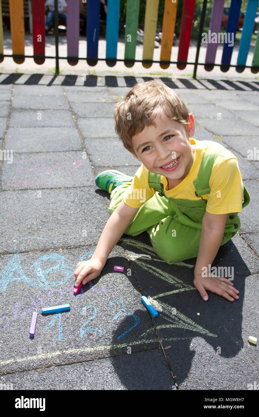 Cute boy write with colored chalks. Little kid draws with chalks. School, ABC and 123 sigh written with colored chalks. Vacation concept. Education. Stock Photo