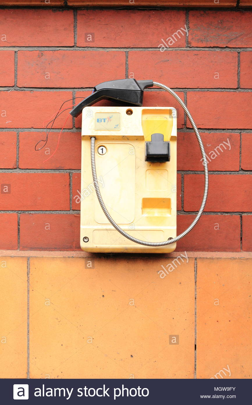 An old, broken British Telecom handset on the wall of the police station at Stalybridge Cheshire England April 2018 - Stock Image