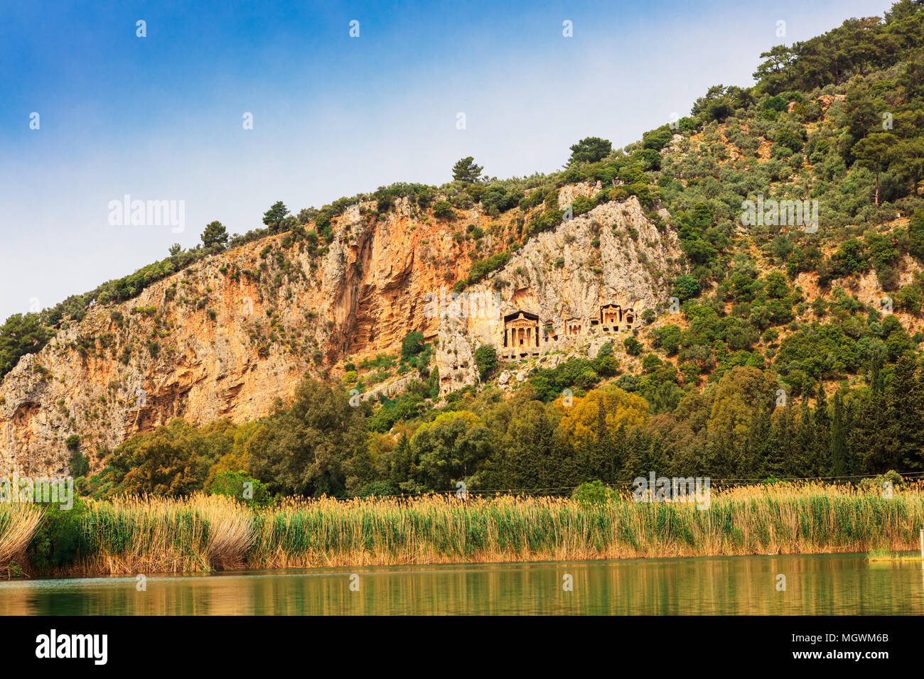 Above the river Dalyan sheer cliffs are the weathered facades of Lycian tombs cut from rock, circa 400 BC. - Stock Image