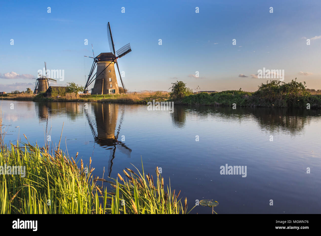 Sunset on windmill reflected in the canal Kinderdijk Molenwaard South Holland The Netherlands Europe Stock Photo