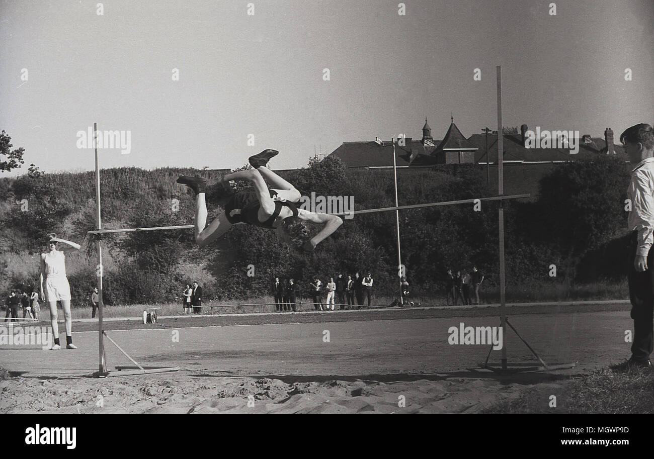1950s, historical picture showing a schoolboy athlete doing 'the straddle' high jump and clearing the bar, England, UK. This technique, face down and legs 'straddllng' the bar, was the dominant style in the high jump up to the mid 70s - Stock Image