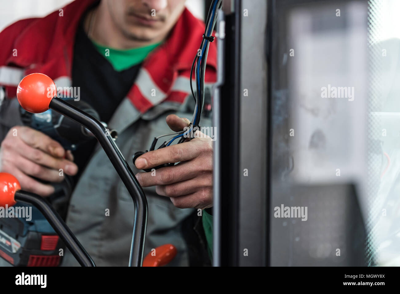 Industrial worker assembles agricultural equipment - Stock Image