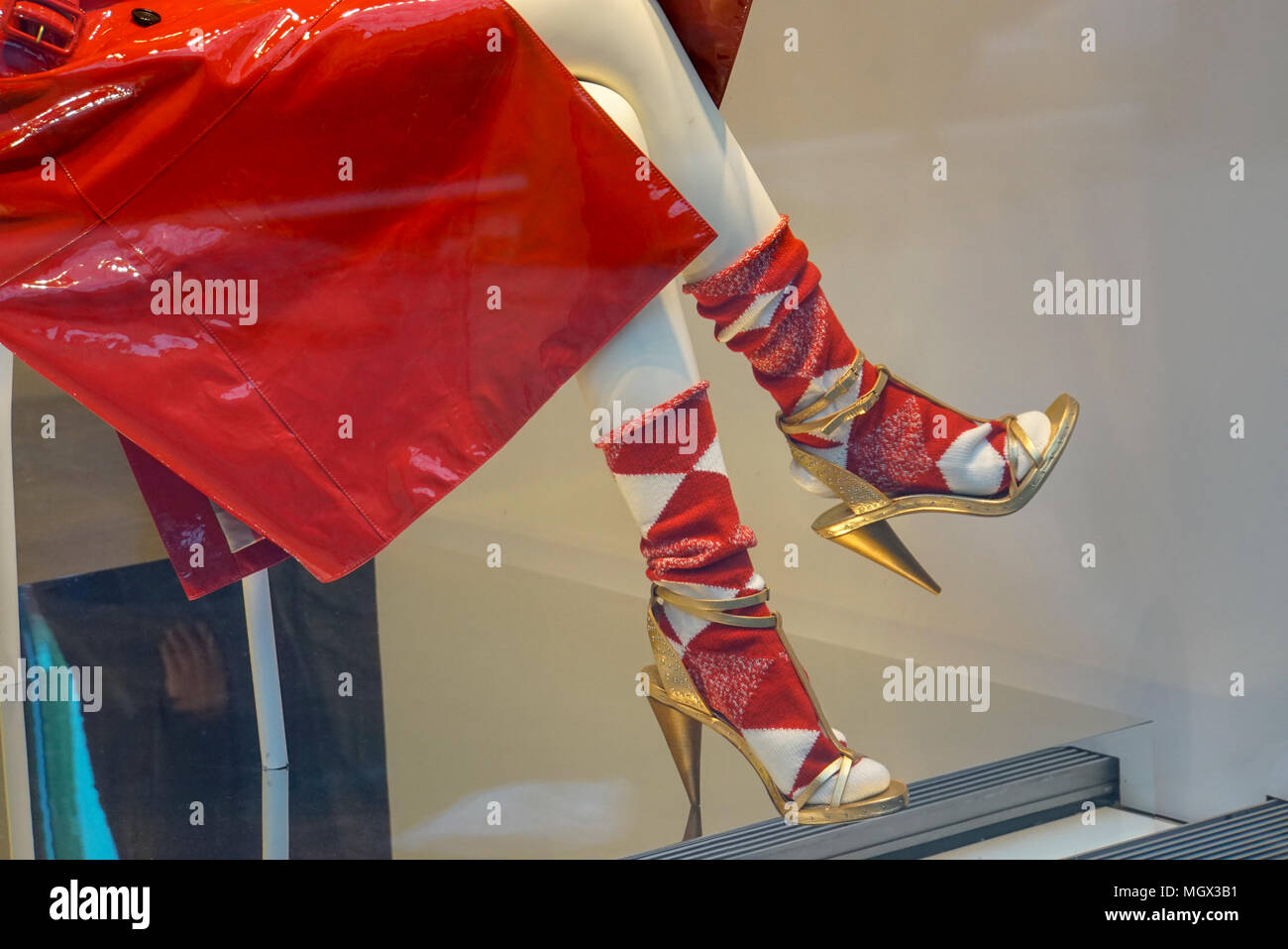 Red raincoat socks and high heel stiletto shoes on a dummy in a shop window - Stock Image
