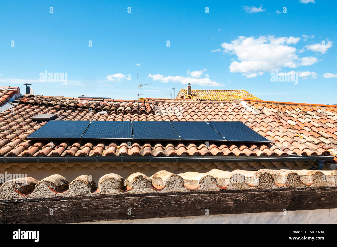 Solar panels on tiled roof of a house in a small Languedoc village in southern France. - Stock Image