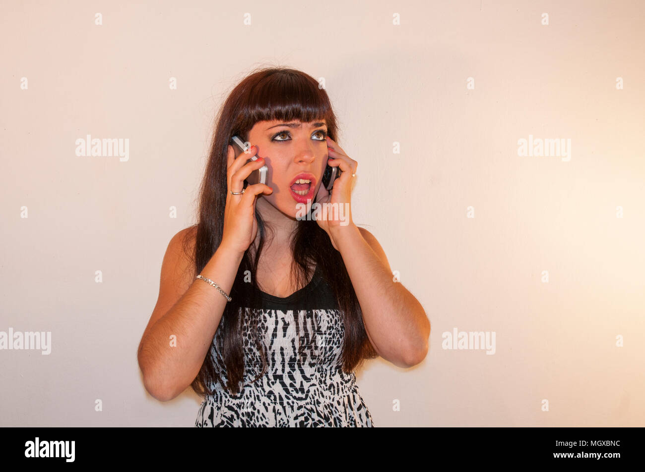Young woman using two mobile phones. - Stock Image