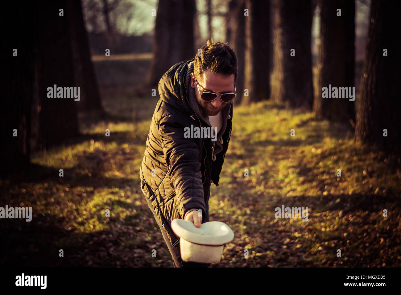 Portrait of a young men, gentleman, with a beard, hat and sunglasses, bowing; outdoor, nature - Stock Image
