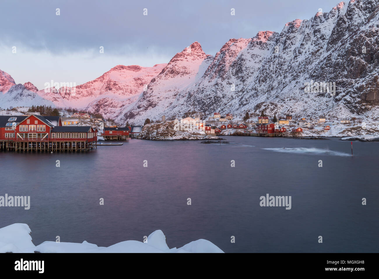 Harbor, rorbuer and snowy mountains at sunrise in A, Lofoten, Norway - Stock Image