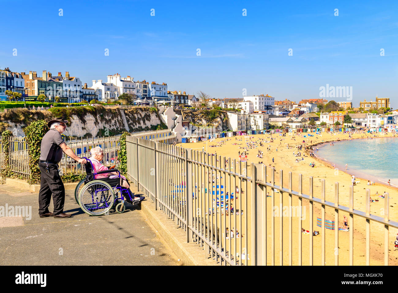 Disabled elderly woman in wheelchair with carer overlooking the beach at viking bay broadstairs Stock Photo